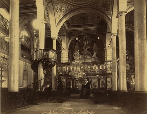 Interior of a Coptic cathedral with seats, iconostasis, icons, chandelier, and a spiral staircase leading to pulpit.